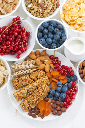 vertical bars: cereal muesli bars, fresh and dried fruit for breakfast, vertical, top view, closeup