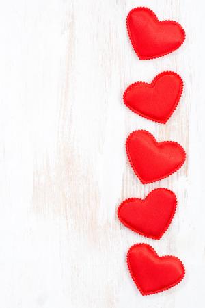 witte houten achtergrond met rode harten, verticaal, bovenaanzicht Stockfoto