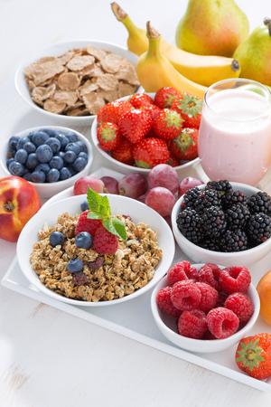 comidas saludables: El desayuno es delicioso y saludable con frutas, bayas y cereales, verticales Foto de archivo