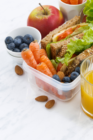 lunch box with sandwich of wholemeal bread on white table, vertical, closeup