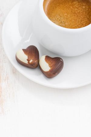 cafe bombon: corazones de chocolate y café express en el fondo blanco de madera, foco selectivo, vista desde arriba, vertical Foto de archivo