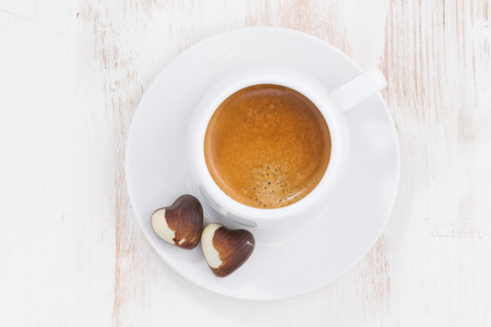 cafe bombon: chocolate hearts and espresso on white table, top view, horizontal Foto de archivo