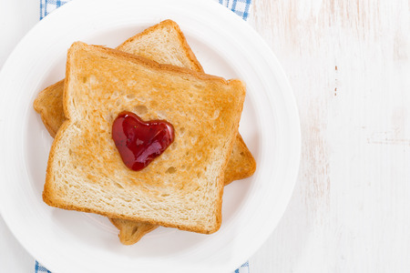 love symbols: toast with jam in the shape of a heart for Valentines Day, closeup top view, horizontal