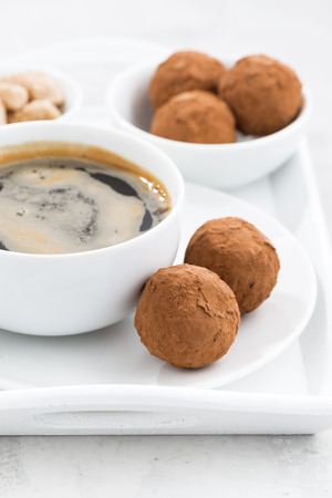 cafe bombon: chocolate truffles and a cup of coffee, vertical, closeup