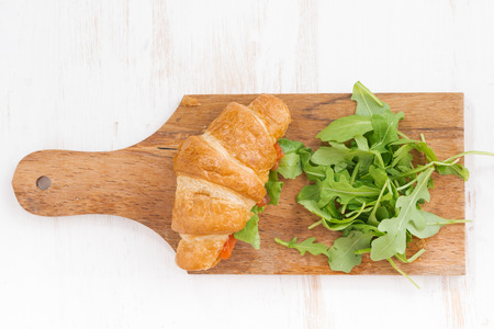 stuffed fish: fresh croissant stuffed with fish and arugula on wooden board, top view, horizontal Stock Photo