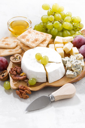 camembert, grapes and crackers on a white table, vertical, closeup Stock Photo