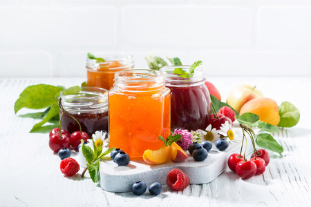 assortment of jams, seasonal berries and fruits on white background, horizontal