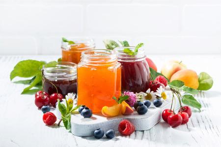 Sortiment von Marmeladen, saisonalen Beeren und Früchten auf weißem Hintergrund, horizontal