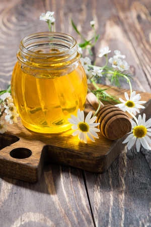 jar with fresh flower honey on a dark wooden table, vertical, closeup