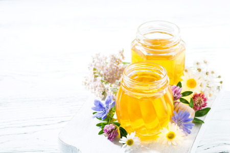 jars with fresh flower honey on white board, horizontal