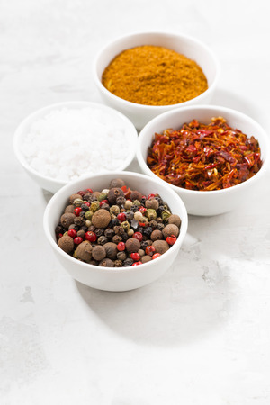 assortment of pepper, salt and spices in bowls, vertical, top view Stock Photo