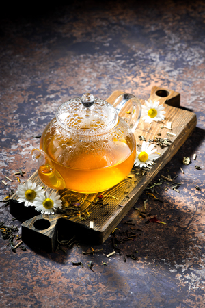 chamomile tea: glass teapot of chamomile tea on dark background, top view