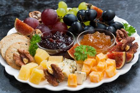 festive appetizers - cheeses, fruits and jams, closeup, horizontal Standard-Bild