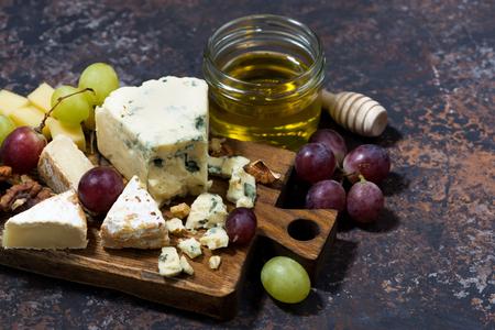 tabla de quesos: tabla de quesos, frutas frescas y miel sobre un fondo oscuro, de cerca Foto de archivo