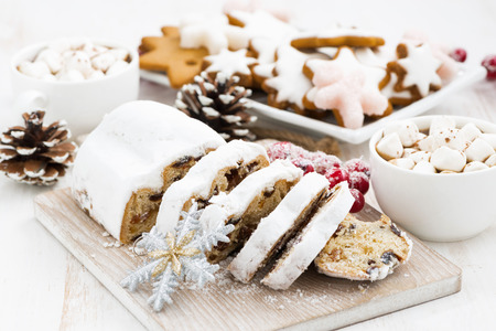 Christmas Stollen on a wooden board and cookies, horizontal