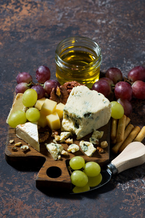 tabla de quesos: cheeseboard, fresh fruits and honey on a dark background, top view