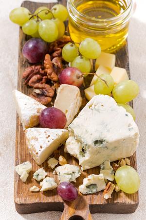 tabla de quesos: tabla de quesos, frutas frescas y miel sobre un fondo blanco, vista desde arriba