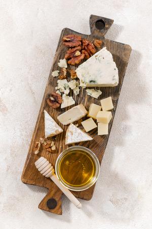 tabla de quesos: tabla de quesos sobre un fondo blanco, vista desde arriba verticales Foto de archivo