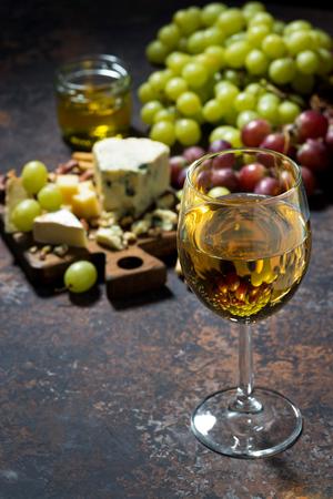 tabla de quesos: tabla de quesos, frutas y vaso de vino blanco sobre un fondo oscuro, vertical, primer Foto de archivo