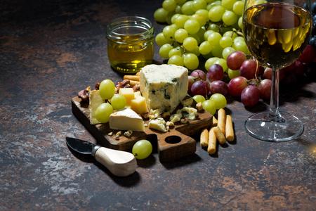 tabla de quesos: cheeseboard, fruit and glass of white wine on a dark background, horizontal Foto de archivo