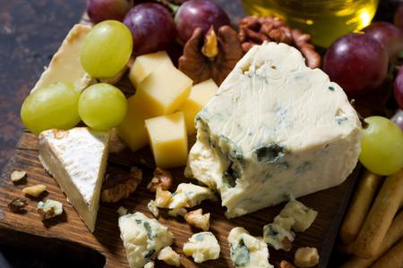 tabla de quesos: tabla de quesos, frutas frescas y miel en una mesa oscura, vista desde arriba, horizontales