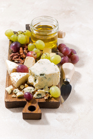 tabla de quesos: cheeseboard, fresh fruits and honey on a white background, vertical, top view
