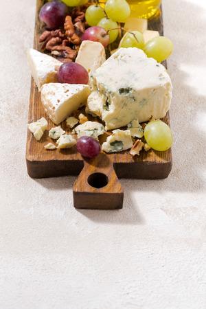 tabla de quesos: tabla de quesos, frutas frescas, miel y fondo blanco, vista desde arriba verticales Foto de archivo
