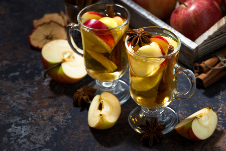 glasses of hot apple tea with spices on dark table, horizontal, closeup