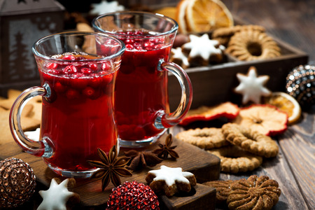 Christmas drink hot cranberry tea and cookies on dark background, closeup, horizontal