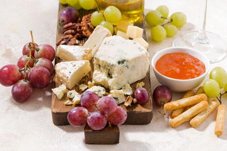 tabla de quesos: tabla de quesos, uvas frescas y miel sobre un fondo blanco, primer plano, horizontal