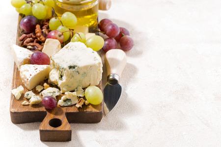 tabla de quesos: quesos, fruta fresca, miel y fondo blanco, de cerca Foto de archivo