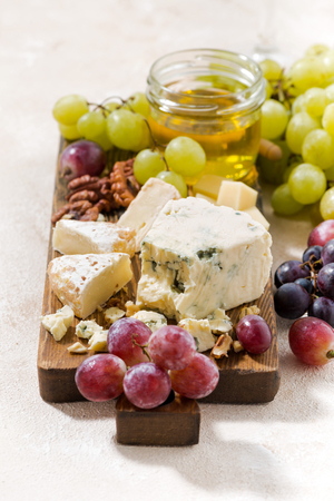 tabla de quesos: cheeseboard, fresh grapes and honey on a white background, vertical, closeup