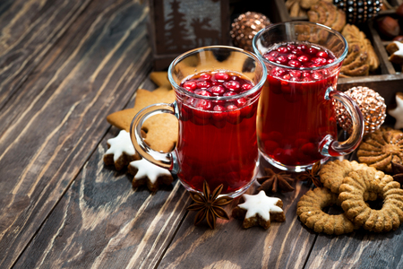 Christmas hot cranberry tea and cookies on dark background, top view