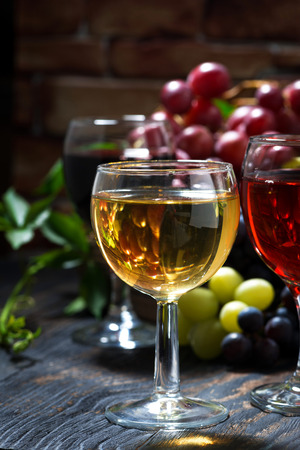 glasses of wine on dark wooden table, vertical, closeup Stock Photo