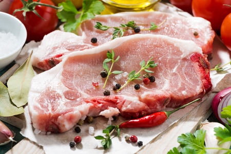 thyme: two pieces of pork on a cutting board and fresh foods, closeup, horizontal Stock Photo