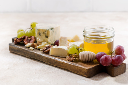 cheeseboard: cheeseboard, grapes and honey on a white background, selective focus, horizontal