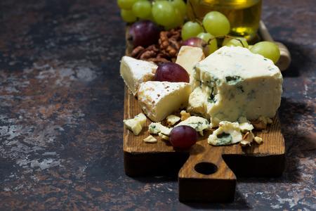tabla de quesos: tabla de quesos, frutas y miel y fondo oscuro, horizontal