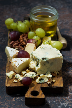 tabla de quesos: cheeseboard, fruits and honey on a dark background, vertical, top view