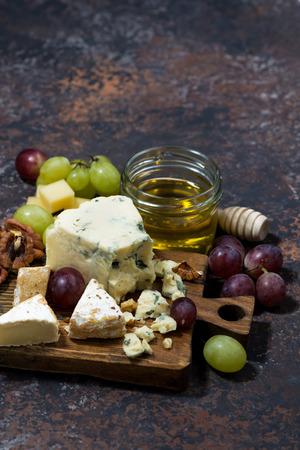 tabla de quesos: Cheeseboard, frutas y miel y fondo oscuro, vertical, vista desde arriba