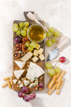 tabla de quesos: cheeseboard, fruits and honey on a white background, top view Foto de archivo