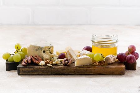 tabla de quesos: Cheeseboard, uvas y miel sobre un fondo blanco, primer