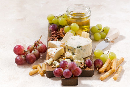 cheeseboard, fruits and honey on a white background, horizontal