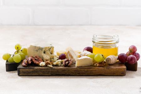 tabla de quesos: cheeseboard, grapes and honey on a white background, closeup Foto de archivo