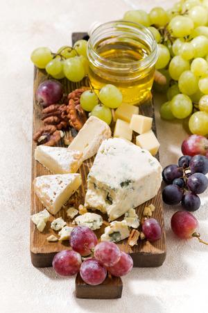 tabla de quesos: tabla de quesos, uvas y vino en un fondo blanco, vista desde arriba