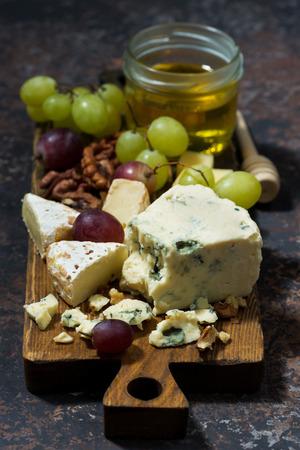 tabla de quesos: Cheeseboard, frutas y miel sobre un fondo oscuro, visión vertical, de arriba Foto de archivo