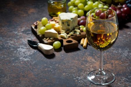 tabla de quesos: glass of white wine, cheeseboard and fruit on dark background, horizontal Foto de archivo