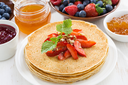 blini: Delicious crepes with strawberries and honey, close-up
