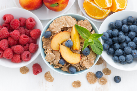 whole-grain flakes with fresh fruit and berries, top view, horizontal