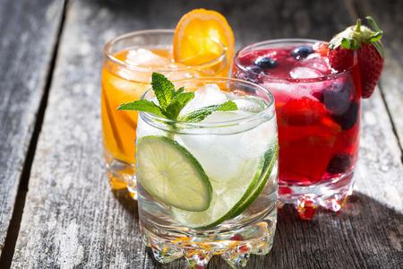 assortment of fresh iced fruit drinks on wooden background, closeup, horizontal