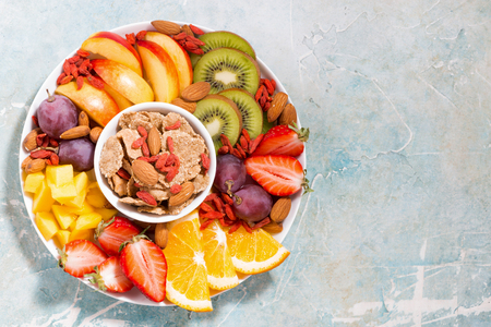 plate of fresh seasonal fruits and cereals, top view, closeup